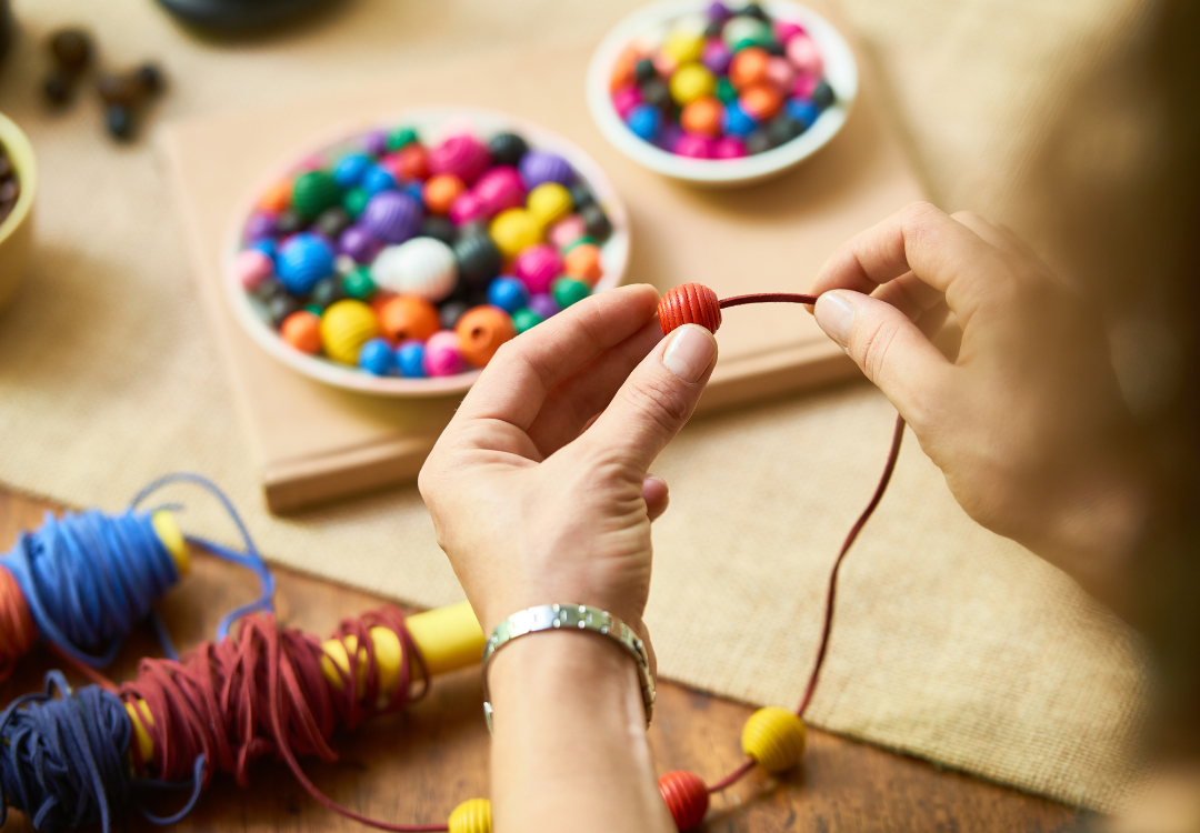close up of a pair of hands making a bracelet with large colourfully painted beads and red and blue thread