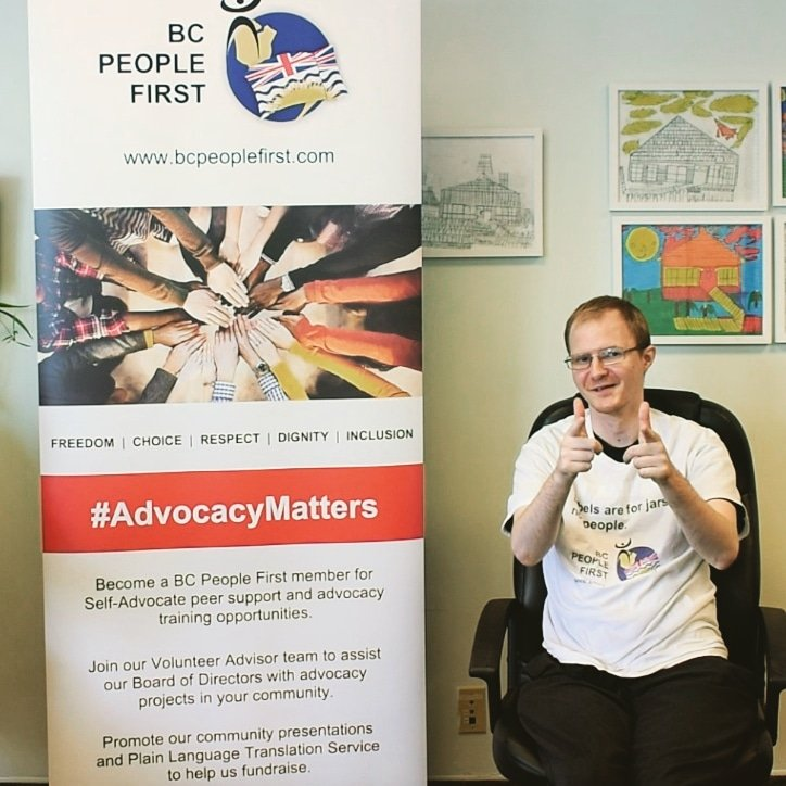 A  person sitting in a chair beside a BCPF marketing banner - they are smiling and giving a thumbs up with both hands