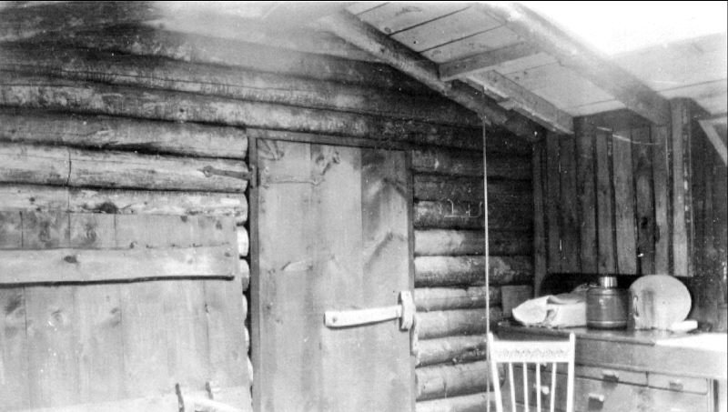 The door in back had a wooden latch with a leather pull. Simply pull it in to lock the door. The rope to the right was to pull up the cooler (a tall box with a screen door). A counter weight was outside the cabin the make it easier and a square floor section sat on top.