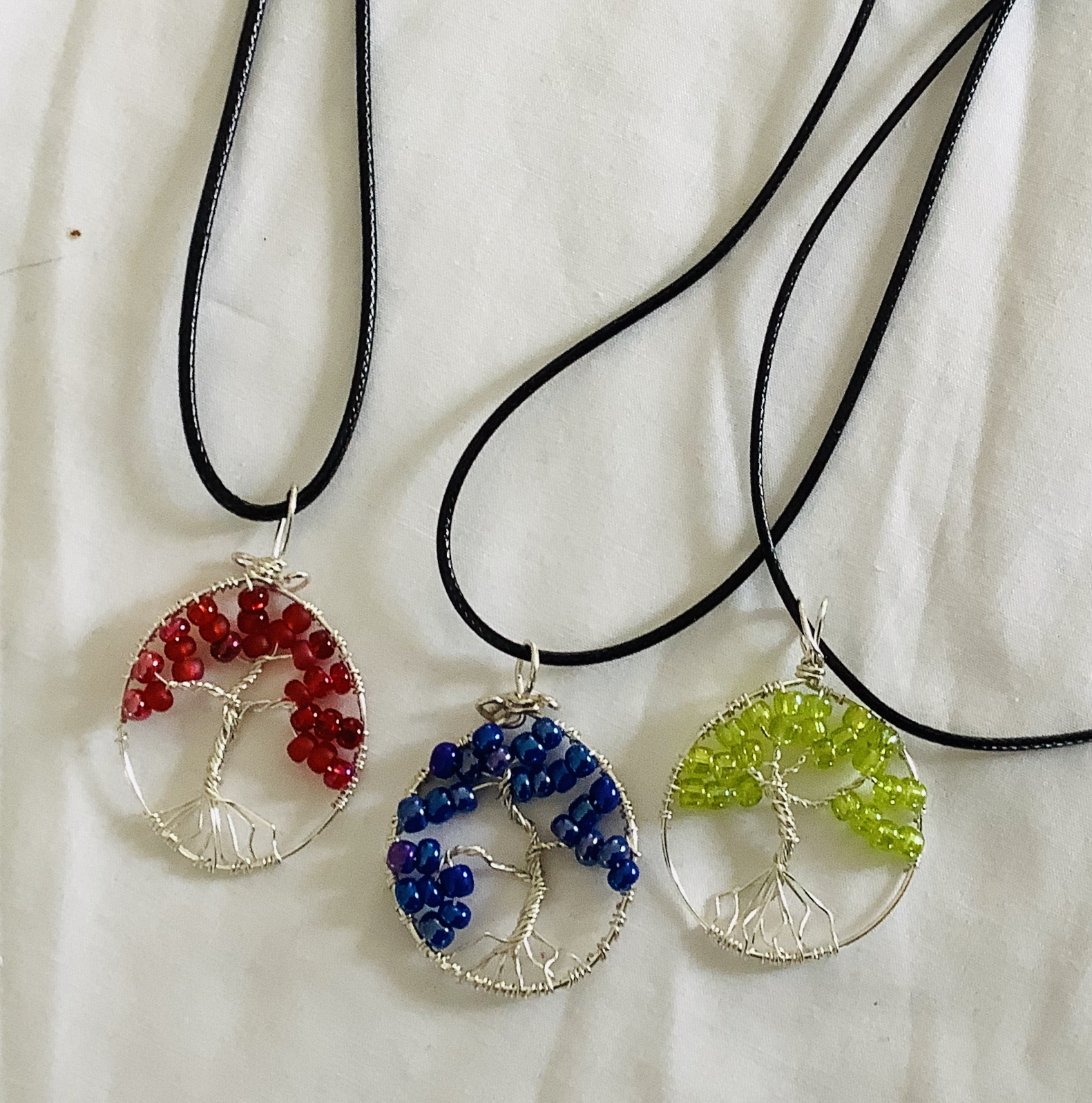 """Trees of Life Pendants has special meaning """"symbol of a fresh start in life"""".  These pendants are hand wired in a myriad of colors, including birthstone colors, family tree colors or any other color of ones choice.   $25.00"""