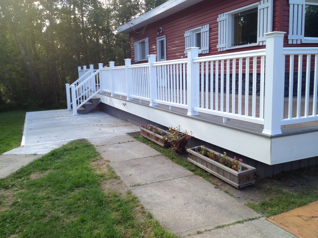Composite deck with railings and concrete pad at landing
