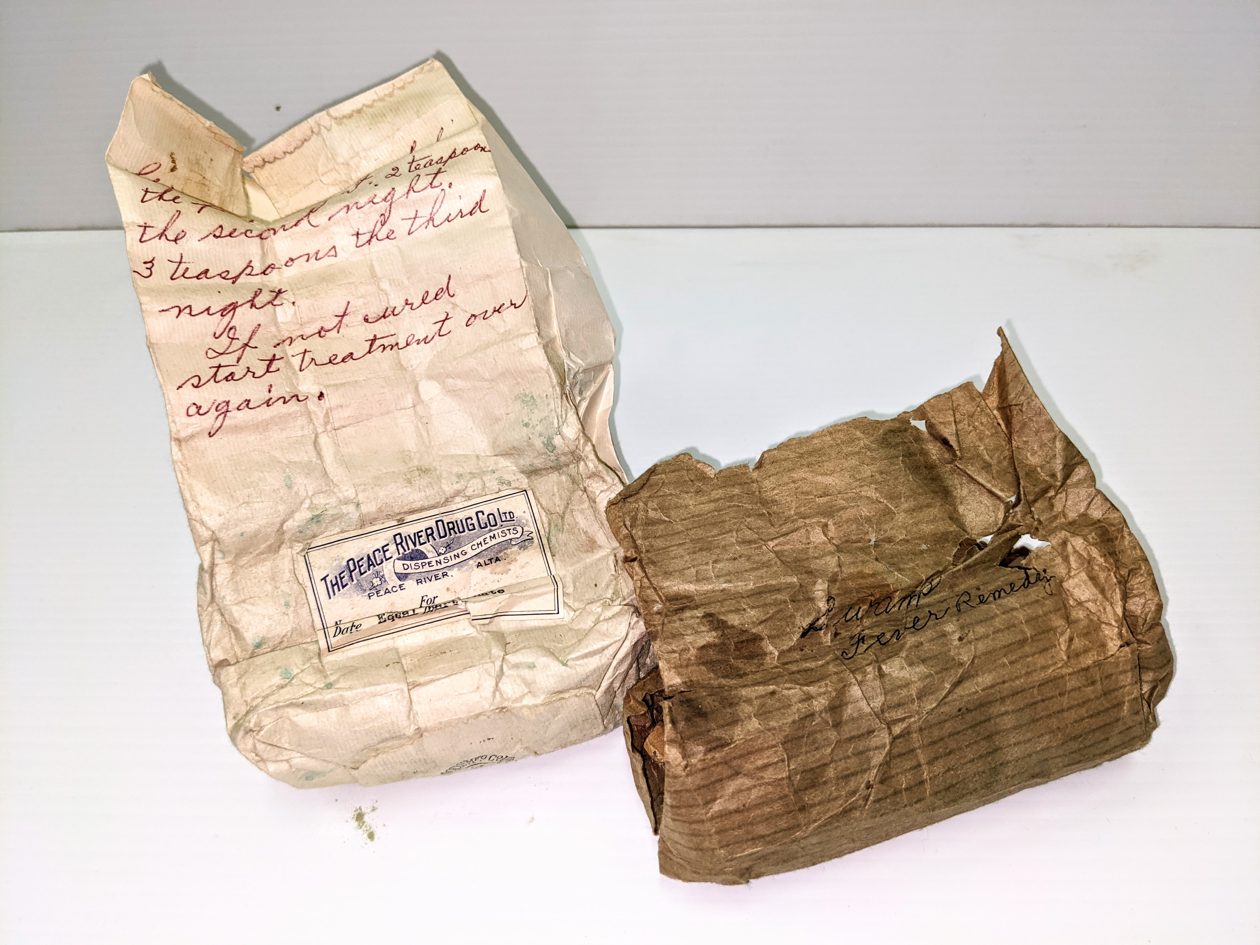 """A product of the Peace River Drug Co. This bag contains a fine green powder labelled as """"Saltpetre, resin, Borax, and copper sulfate"""". Scribbled on the brown packaging its use is labelled as """"For Swamp Fever"""" while the red pen dictates the correct dosage. """"1 teaspoon the first night, 2 teaspoon the second night, 3 teaspoon the third night. If not cured start treatment over again"""". Swamp fever is an ailment in horses that causes lethargy, muscle atrophy and anemia - not ideal for indigenous folks and pioneers who relied on horses for transport and heavy work!  14/06/2021 2000.03.54 / Cambell, Jean"""