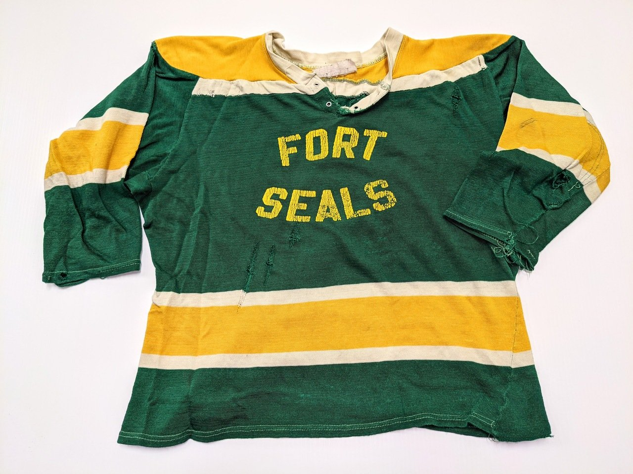 """This hockey Jersey comes from the oldest Hockey Team in Fort Vermilion - The Fort Seals. Sponsored by the S. Stephens store this team dates back to the 1940's. The Jersey is small in stature with short sleeves and  wide dimensions typical of a goalie jersey to accommodate extra padding. We do not have information on the significance of the name """"Seals""""  05/07/2021 2020.59.23/ Smith Louise"""