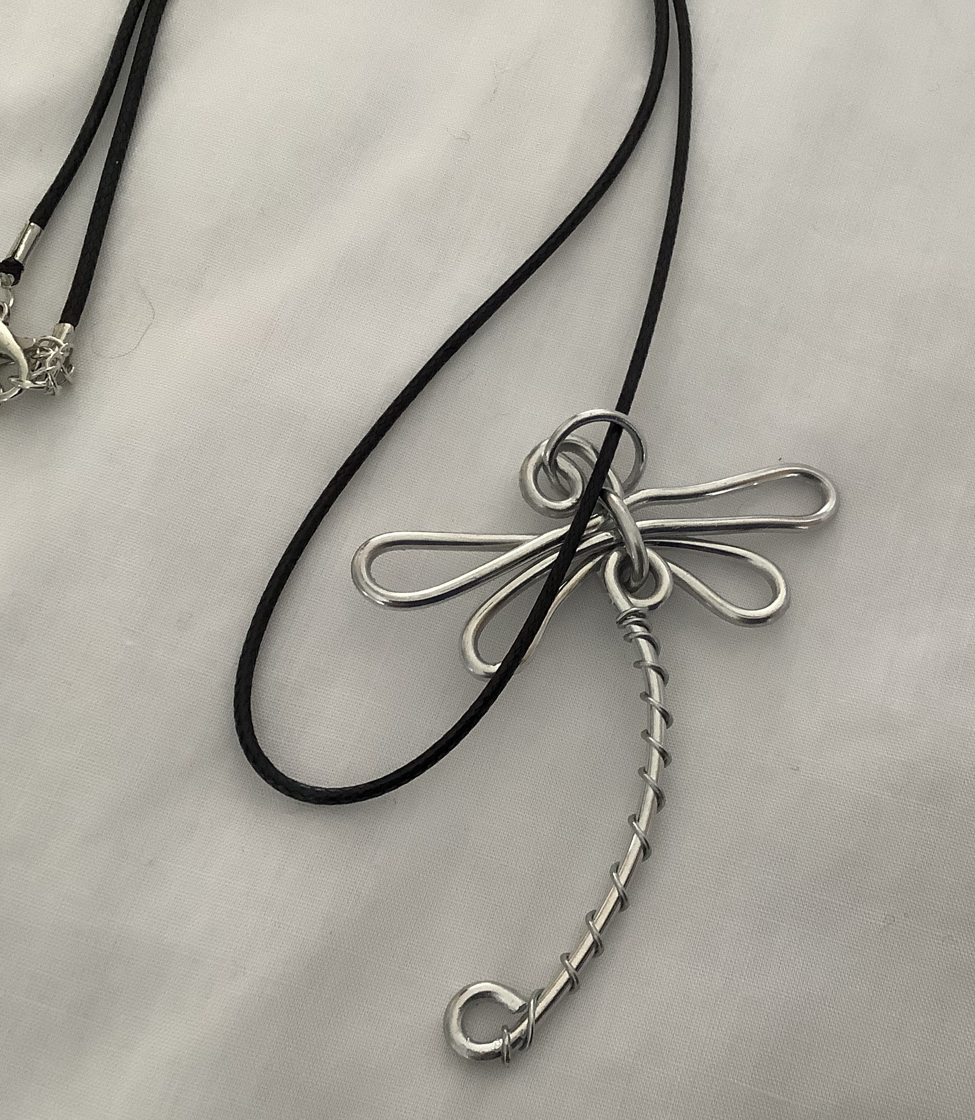 """Dragonfly Pendant is hand wired using silver or aluminum wire.  The """"Dragonfly"""" symbolizes change, transformation adaptability and self-realization. If a dragonfly lands on you it is a sign of good luck.  Price $30.00"""