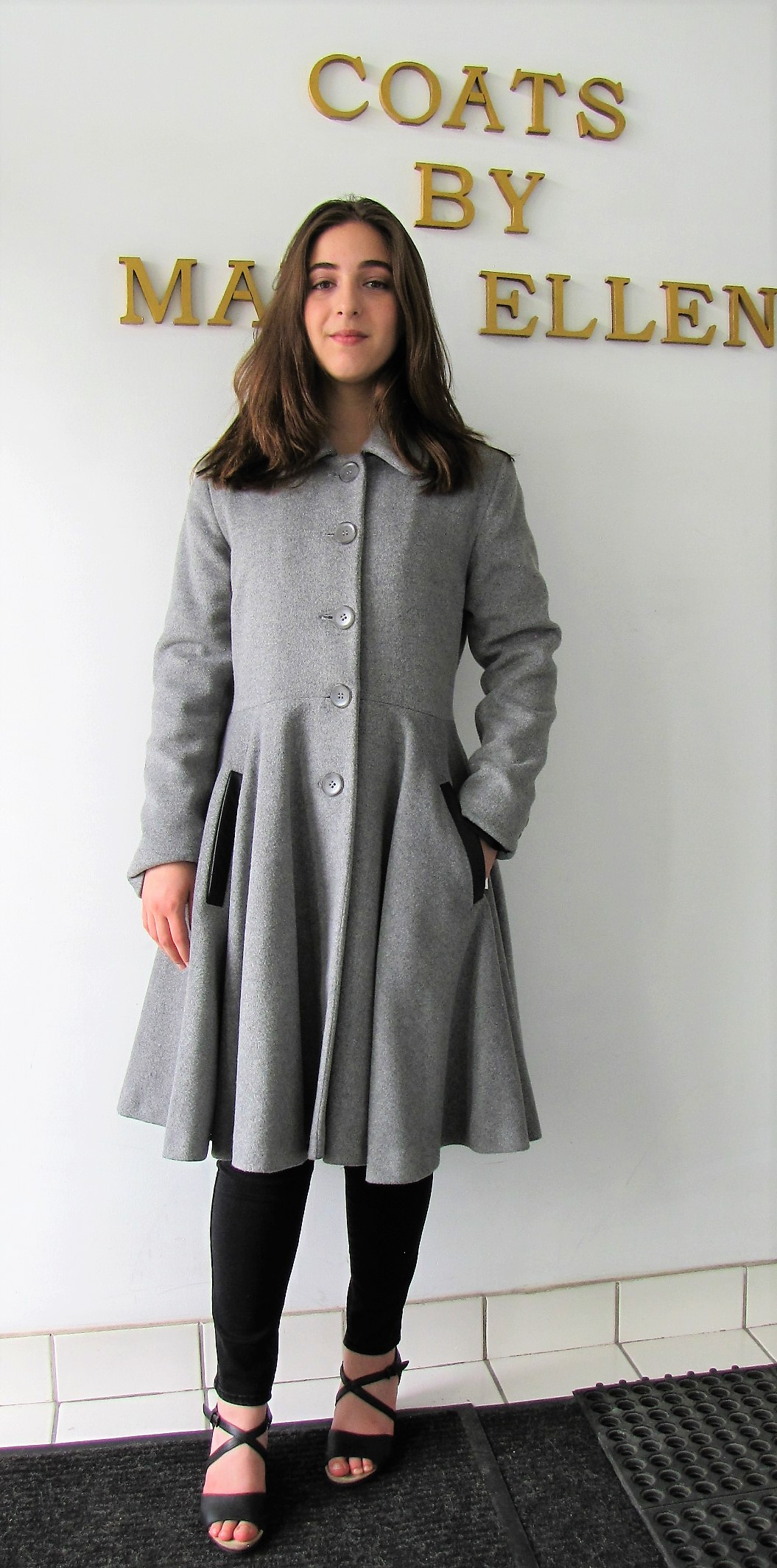 Style #10291-7  Smoke Grey  50% Cashmere/ Wool  Features: Feminine and elegant.  Inspired by the early 1950's.  Put this coat on and you'll feel just like a princess! Genuine Lambskin Leather Trim Chamois lined. Extra buttons included.  In-Stock Colours: Smoke Grey, Houndstooth, Winter White, Black or can be custom made in the colour of your choice.  Various Fabric: Cashmere or Cashmere Blend, Alpaca, 100% Pure Virgin Wool or can be custom made  in the fabric of your choice.  Size: S,M,L  Price: $ 650 and up