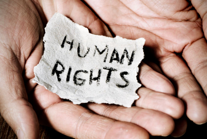 two hands open together and holding a piece of paper that says human rights