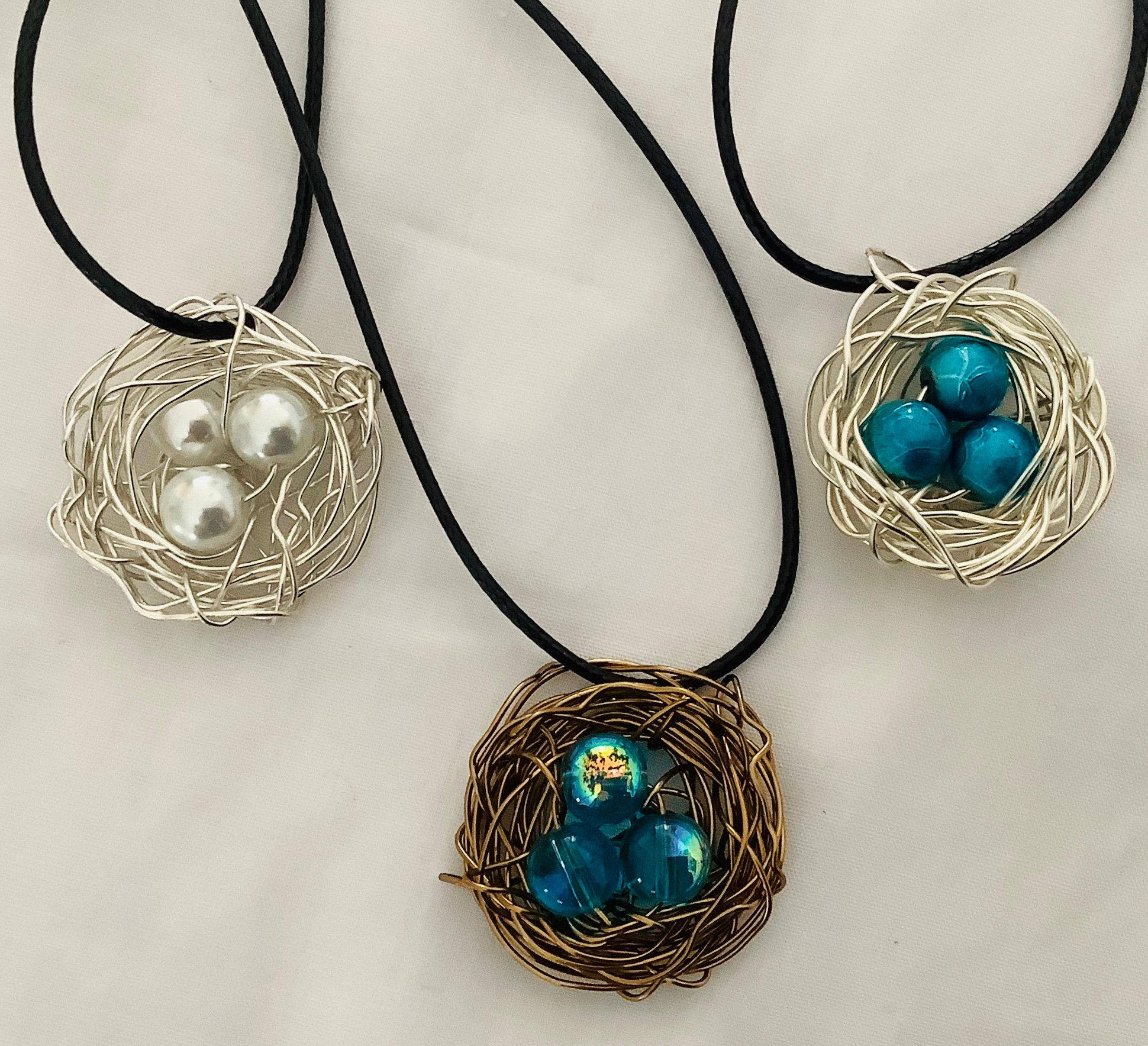 Bird Nest pendants are handwired individually using several types of wire and blue or white bead for the eggs. Any number of eggs can be added to the nest. Some folks have ordered the number of eggs of their family members.   $30.00