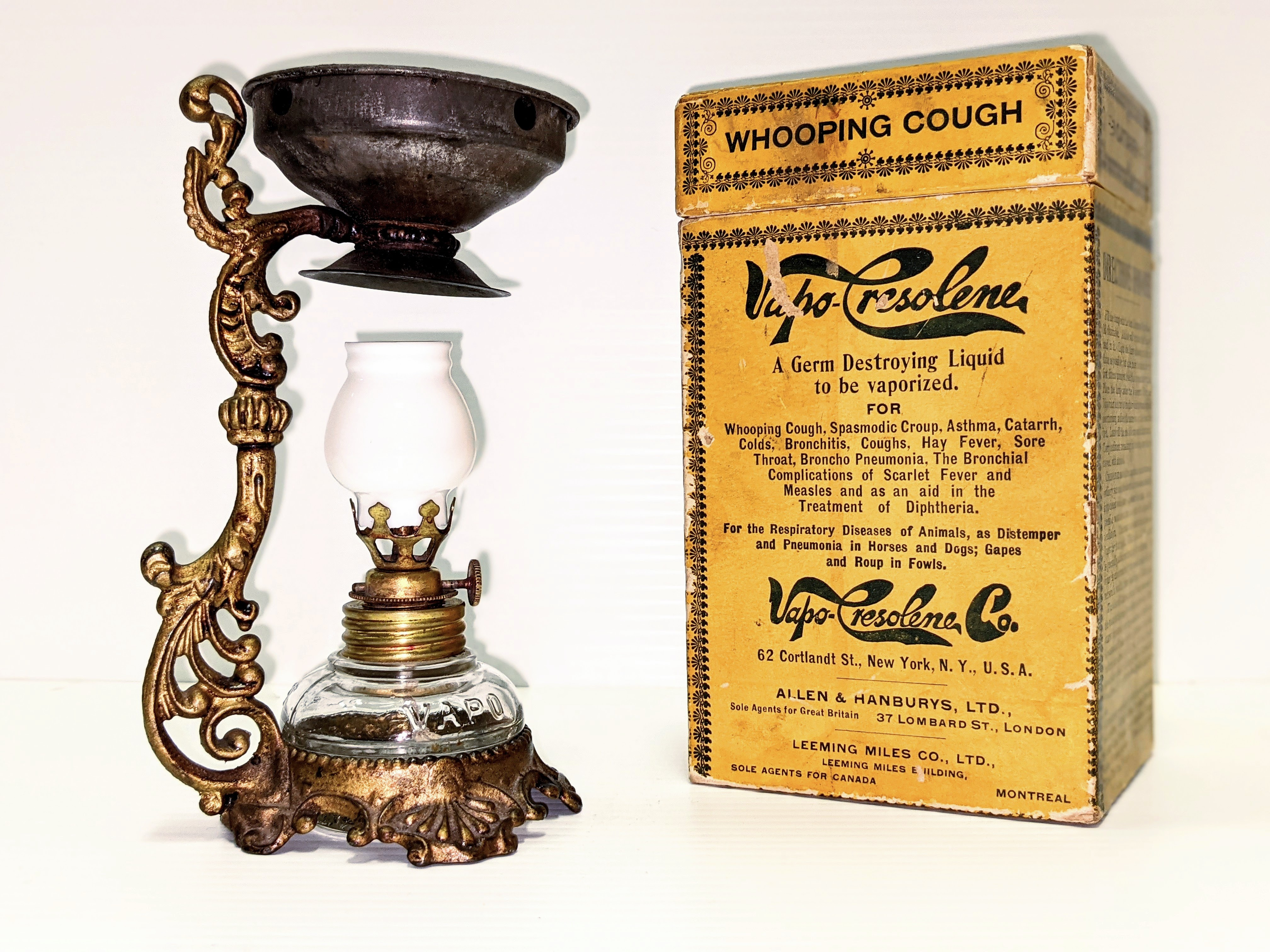 """Jack Whitehouse gifted this Vapo-Cresolene Lamp to Magdaline (Smith) Lapp in 1921. The lamp was used to keep the family healthy while living in Hay lakes and Fort Vermilion. The small kerosene lamp at the base would heat the """"Germ destroying liquid"""" Cresolene placed in the dish above. Used to treat causes such as Diptheria, Scarlett Fever, Asthma, Whooping Cough and a host of others - it is also noted as effective treatment for respiratory diseases of animals.  29/03/2021 2020.87.1-3 / Ward, Mina"""
