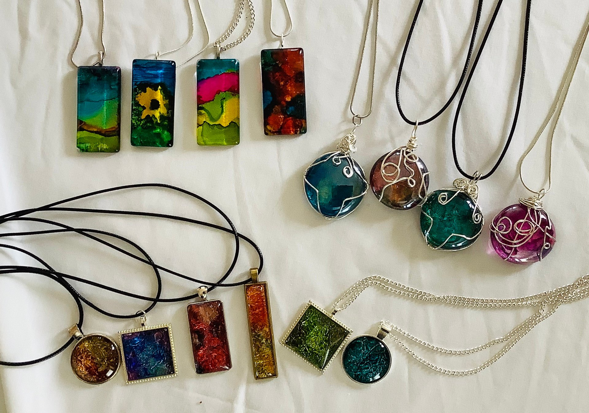 Alcohol Ink Pendants are individually hand painted in several styles and settings. Some are set in a tray while other are hand wired. Price $25.00 - $45.00