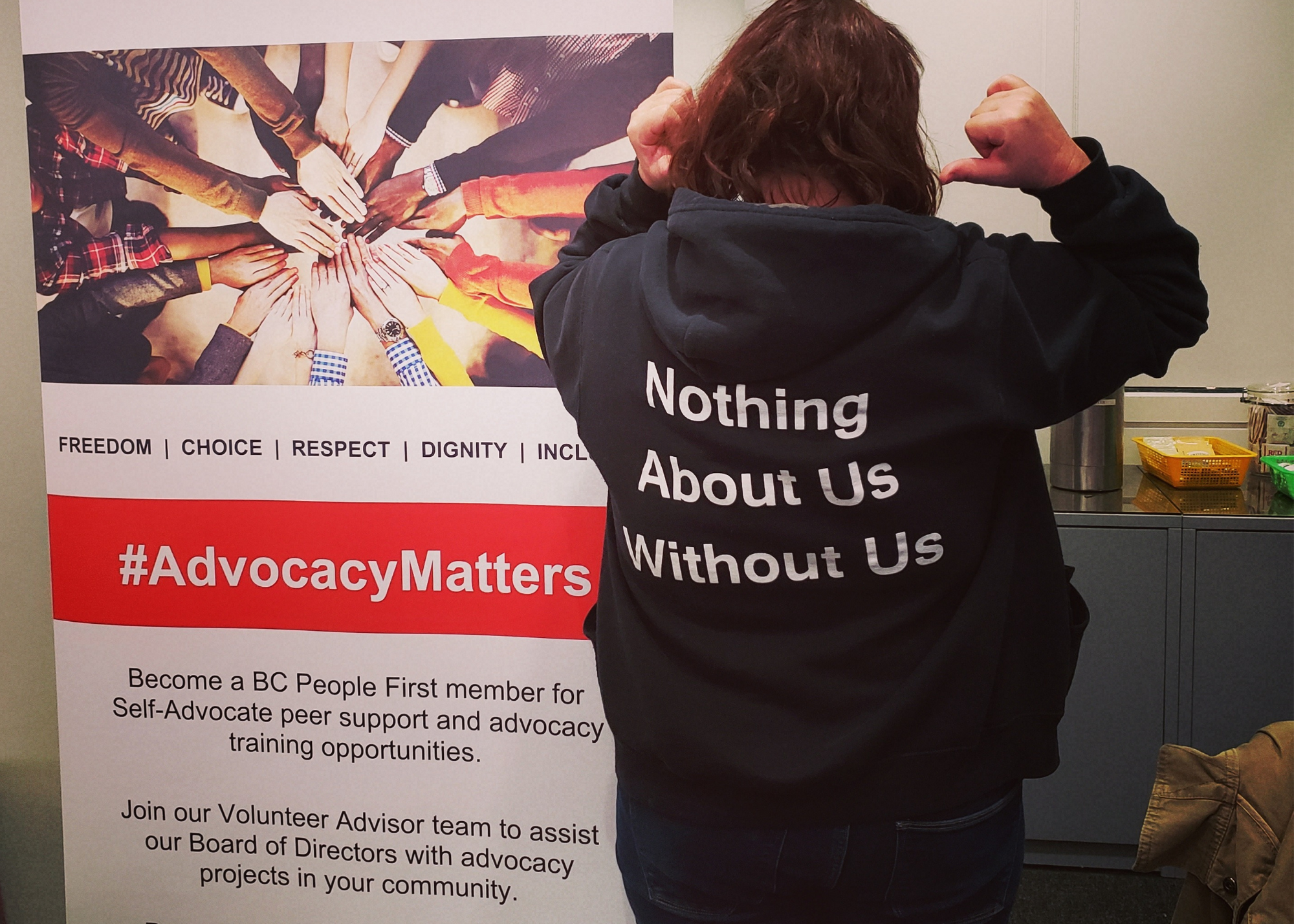 "Person standing beside a marketing banner - they are facing away from the camera and pointing to the back of their shirt that says ""nothing about us without us"""