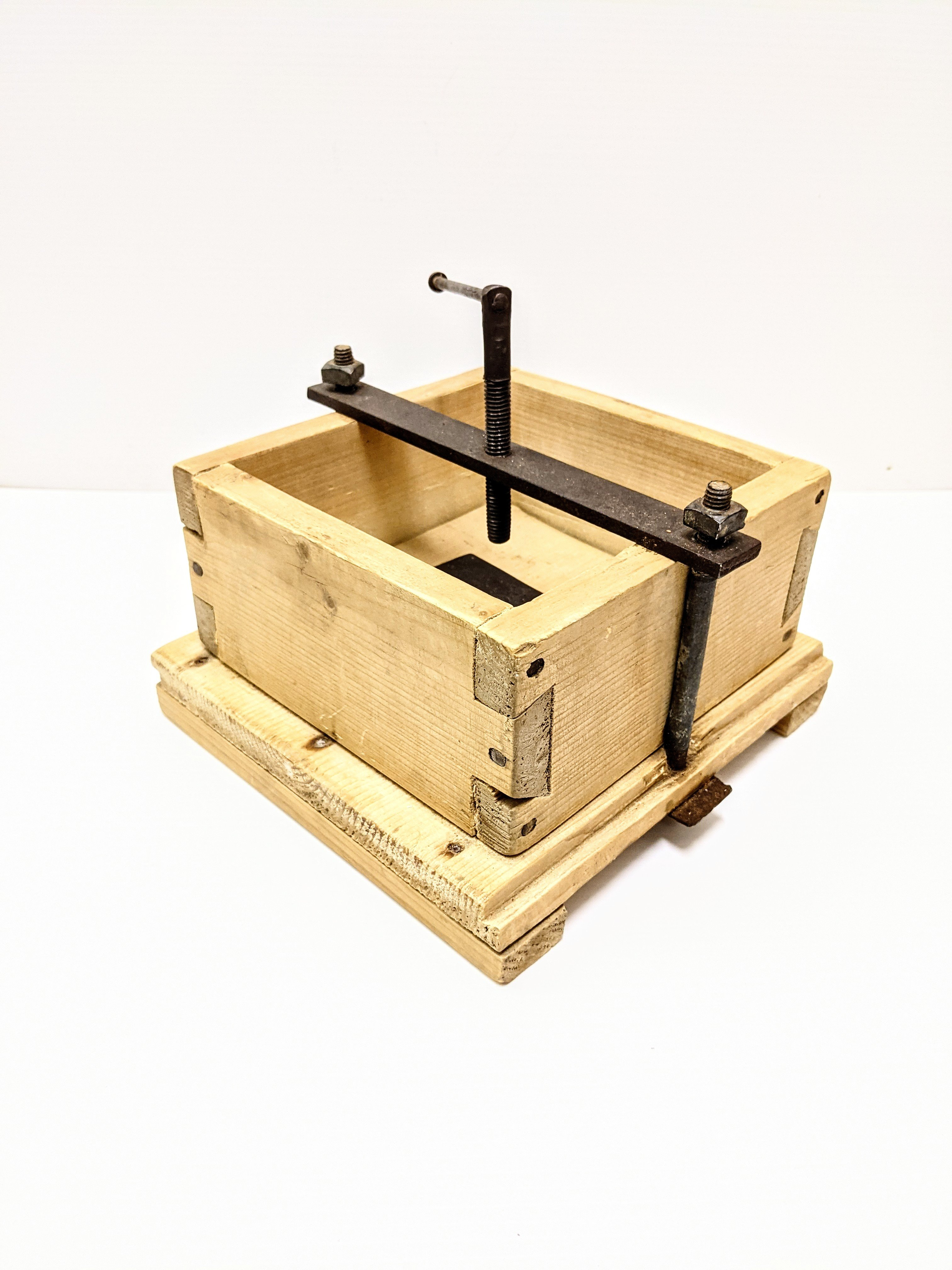 This artifact of the week is a food press from the Trapper Shack. A homemade affair, this large block likely was used to press cheese or butter. Upon close inspection one can see the remains of such food products pressed into the wood base and sides. Holes are drilled in the base to allow for drainage of the inserted food item. Notice the expertly carved dove tail notching holding the box together - an important feature for this box that would be under pressure/ stress for extended periods of time!  10/05/2021 2007.47.11.1 / Trapper Shack