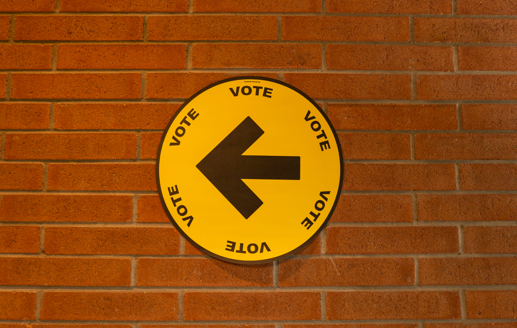 A brick wall with a vote sign in the centre including a left direction arrow. in the centre of the vote sign.