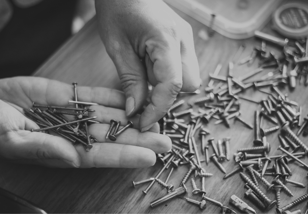 a black and white photo of a person's hands sorting screws by size over a table top