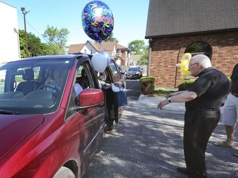Archdeacon Matthewman greets a vanload of participants. DAN JANISSE photo