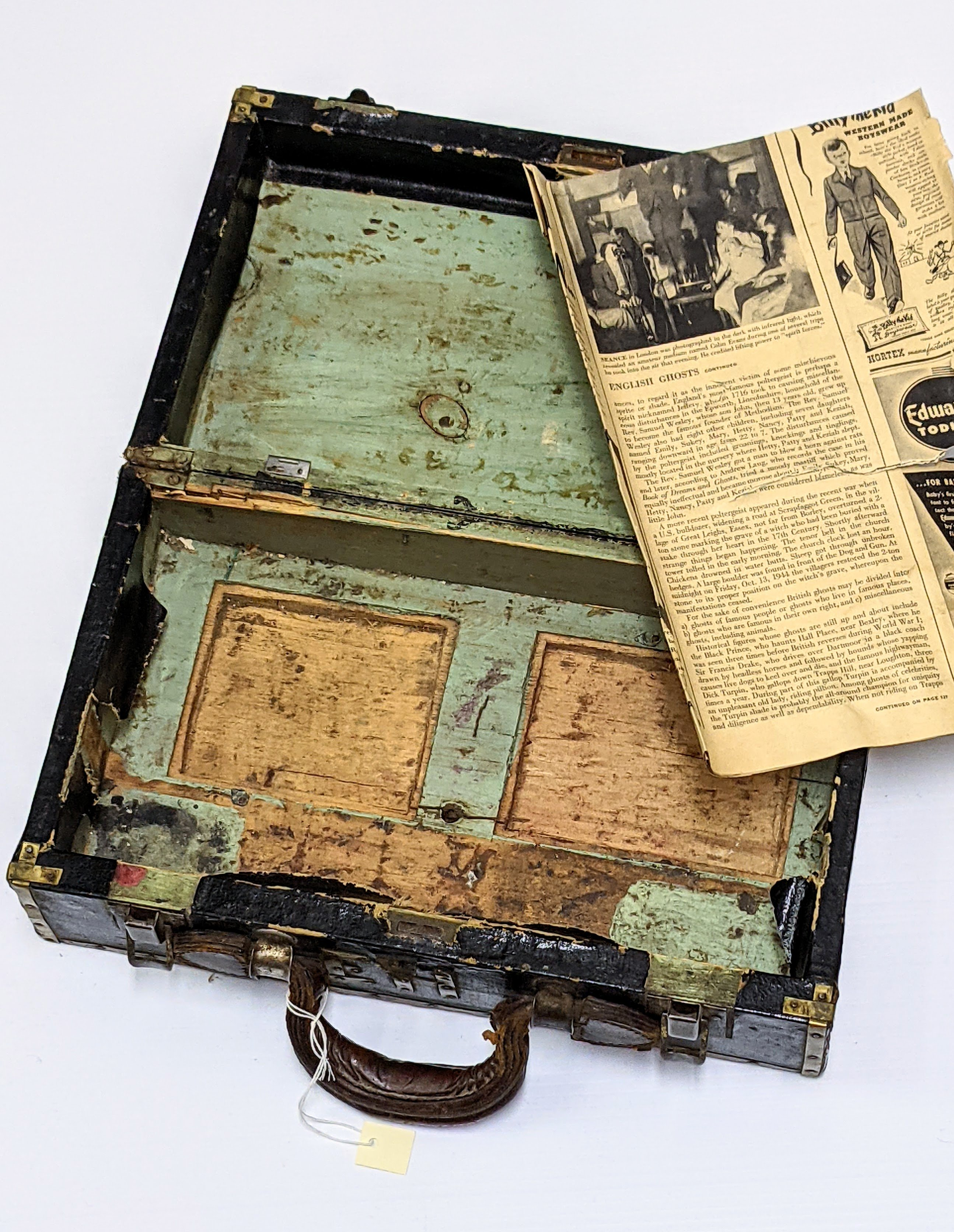 """We believe this to be a protective case. For what exactly we are not sure. It is a bit large for jewelry, though does have the Initials """"EH"""" stamped on the front indicating it to be a personal item. The paint markings, hollowed base, and extra hinges indicate secret compartments or other elements no longer present  The inconsistent work on of the trim and fabric covering indicate it was homemade or repurposed from it's original use. The newspaper was found inside as a bottom and gives us a ball park estimate on the age of the artifact. The paper comes from the September 22, 1947 issue of Life Magazine!  If you have any insight on its purpose - please let us know!  08/08/2021 2007.61.20 / Tourangeau, Martha & Harvey"""