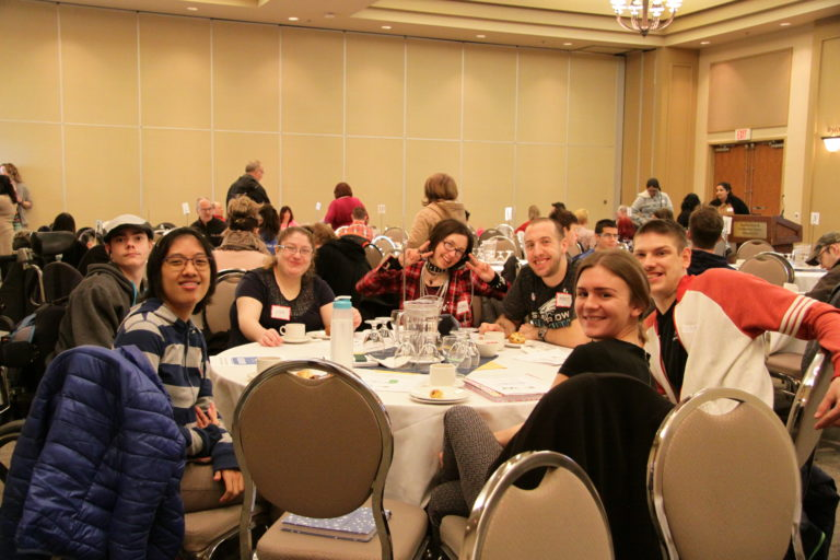 A group of People First Members sitting around a table at a BCPF event