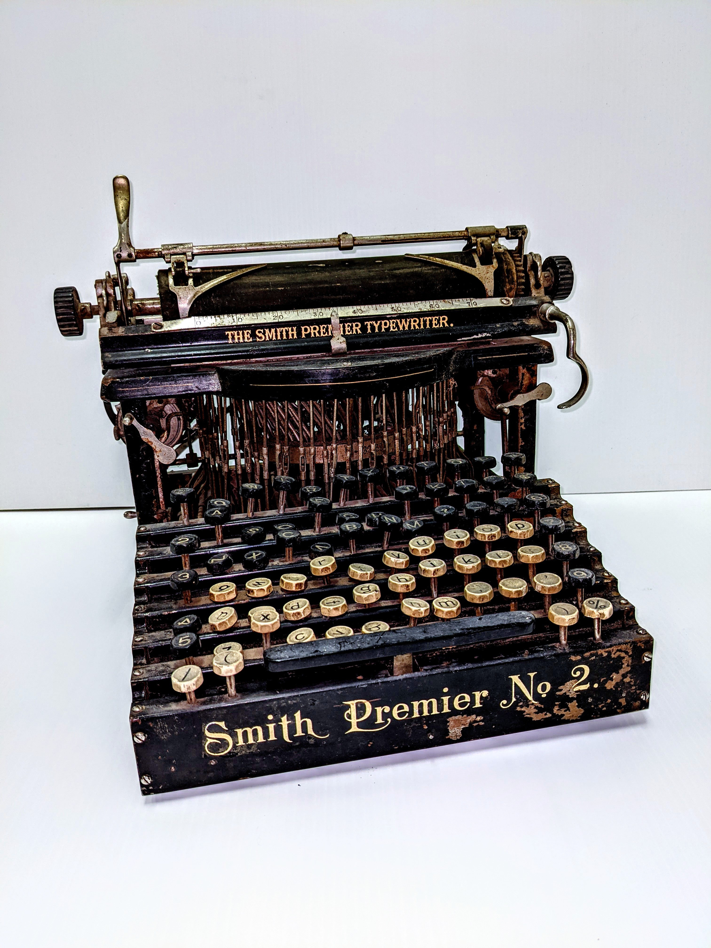 This Smith Premier No 2. Typewriter dates from 1904.  This typewriter has 2 full keyboard sets (one of upper case and one of lowercase) and uses an upstrike mechanism which makes it a 'Blindwriter'. Using this machine the typist cannot see what they are typing until they flip up the page roller mechanism. This differs from the 'modern' or 'visible' typewriter in which the typists sees what they are typing.  Another unique feature is the hand cranked cleaning brush for cleaning the typebars.   15/03/2021 2004.03.04 / Twidale, John & Alfa