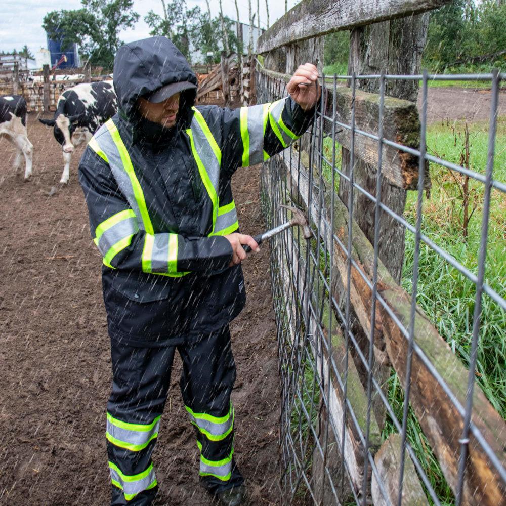 https://0901.nccdn.net/4_2/000/000/06b/a1b/sj35-sb04-farmer-mending-fence-in-the-rain-wearing-safety-rain-j.jpg