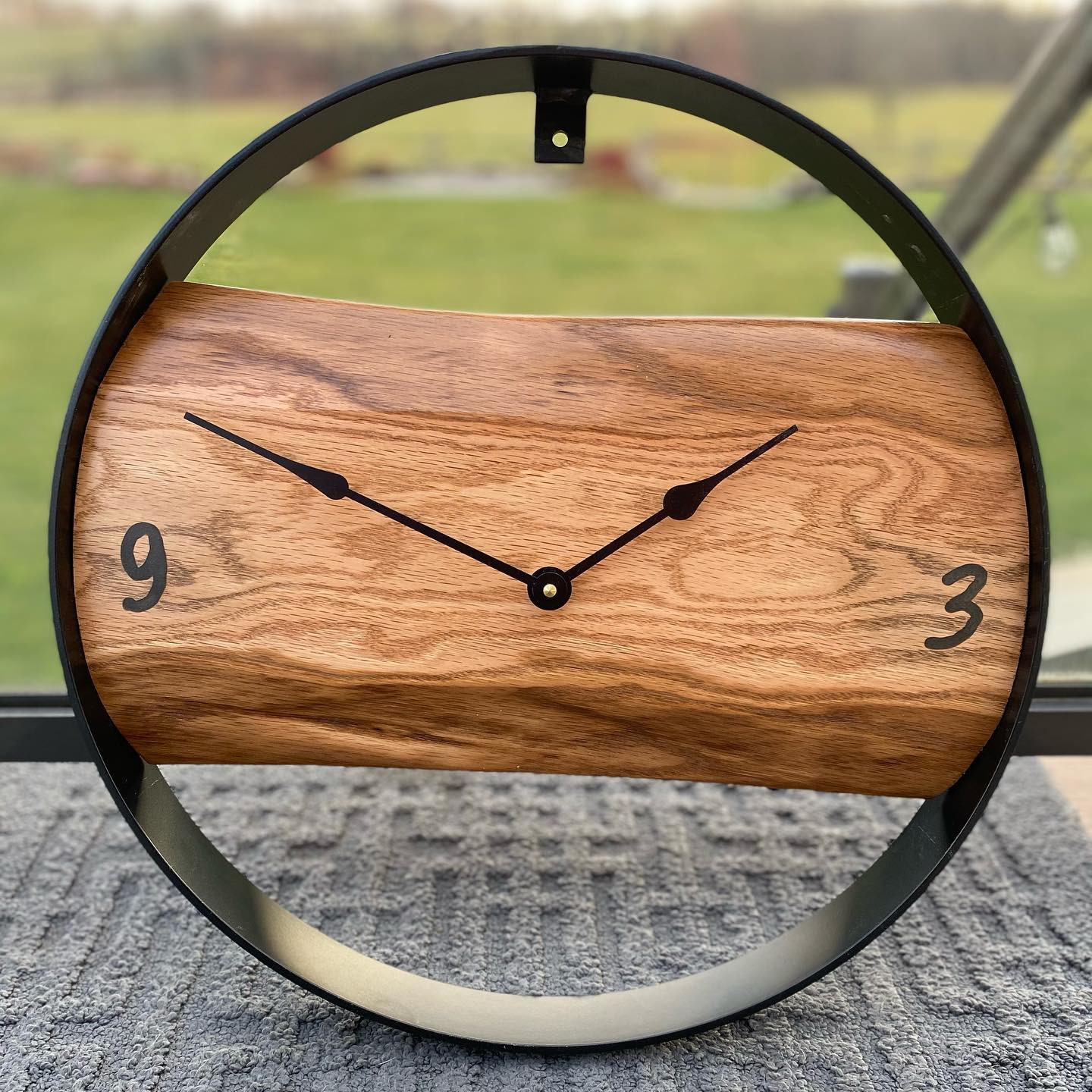 """18"""" Oak Clock  Simplicity makes a statement with this particular piece. Stained fruitwood and finished with satin polyurethane. The numbers are hand carved with a trimmer router and filled with stone tinted resin epoxy. Powered by high torque Quartz movements. The clock parts were provided by Craftime Clockery, in Arthur, Ontario. The metal ring sourced at Taylored Custom Fab in London, Ontario. $149"""