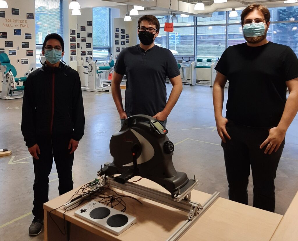 UBC Engineering students Keith, Nicholas, and Scott look over an Arm Cycle Gaming Interface prototype they developed. Photo Credit: ICORD
