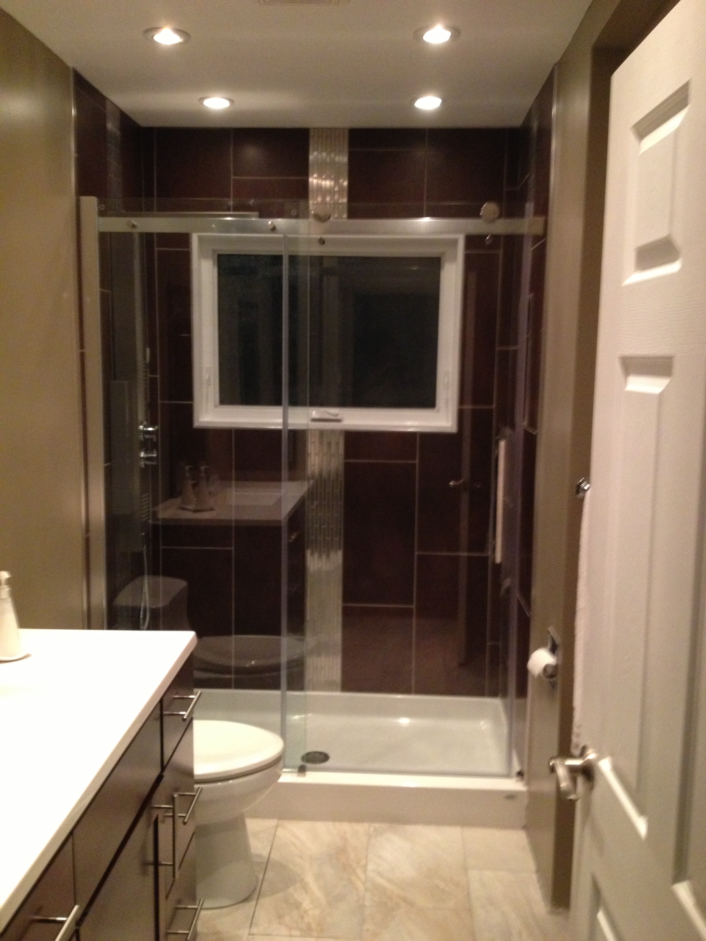 Bathroom remodel with sliding glass door in shower and recessed lighting