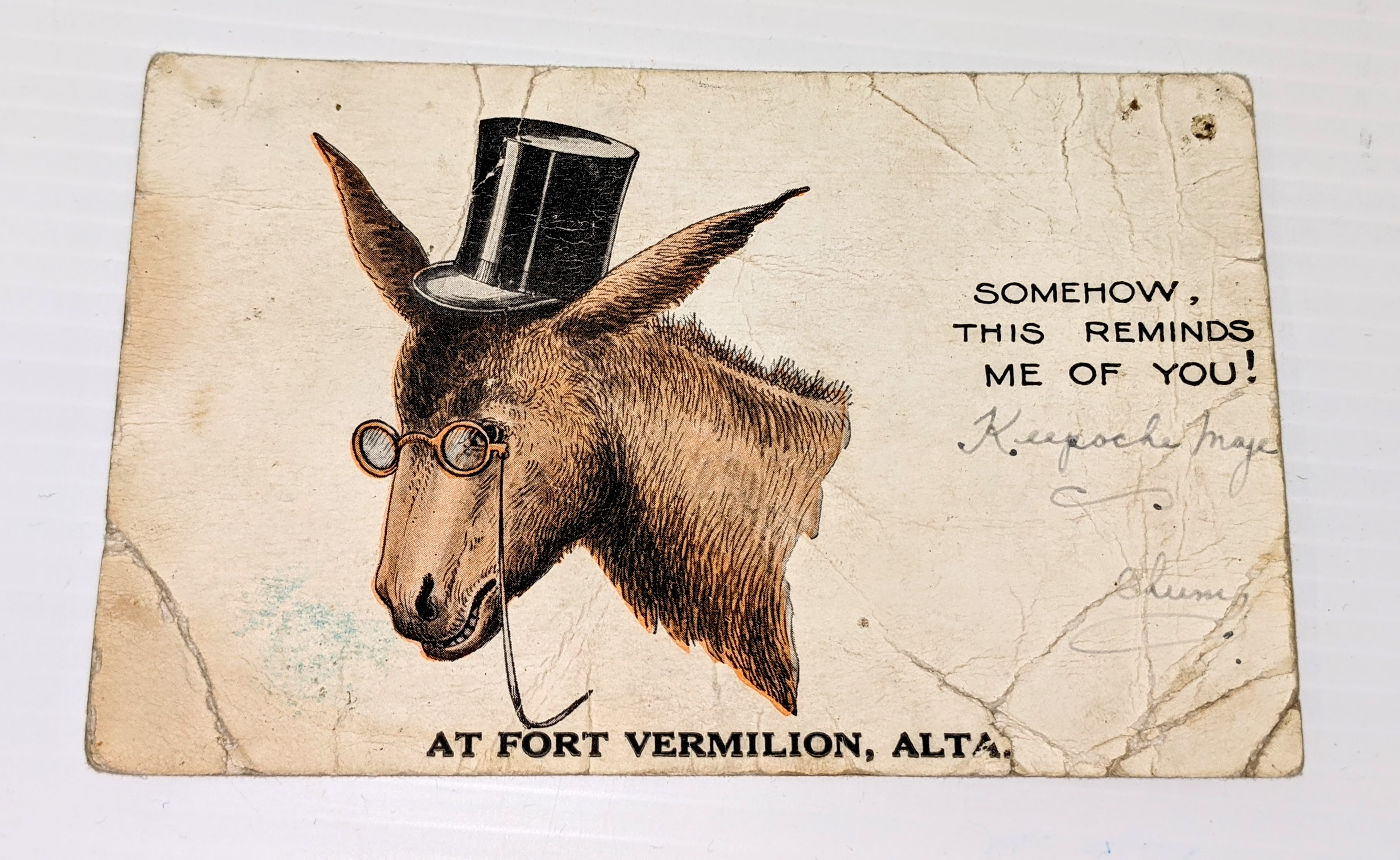 """This is a postcard for Fort Vermilion from 1934. Made in the United States, the brand is """"Donkey Comics"""" and who made generic postcards that any town or locale could add their title too. Considering the age of the post card the Board of Trade likely put the """"At Fort Vermilion"""" stamp on it. The card is not signed nor has been sent. You'll notice on the right hand side a few words in cursive - we can't quite understand them so if you can please let us know!  16/08/2021 2001.17.01 / Mcleod, William A."""